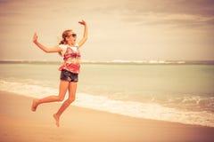 Muchacha adolescente feliz que salta en la playa Imagen de archivo libre de regalías