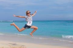 Muchacha adolescente feliz que salta en la playa Foto de archivo libre de regalías