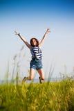 Muchacha adolescente feliz que salta sobre el cielo azul Muchacha de la belleza que tiene el ou de la diversión Fotografía de archivo libre de regalías