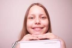 Muchacha adolescente feliz que se sienta con el libro Fotografía de archivo libre de regalías