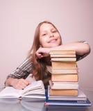 Muchacha adolescente feliz que se sienta con los libros Foto de archivo libre de regalías