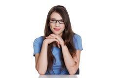 Muchacha adolescente feliz que se sienta en el escritorio Foto de archivo libre de regalías