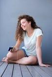 Muchacha adolescente feliz que se sienta en el piso que escucha la música Fotos de archivo libres de regalías