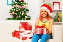 Muchacha adolescente feliz que se sienta en el sofá con los presentes Foto de archivo