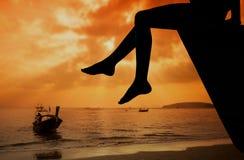 Muchacha adolescente feliz que se sienta en la playa en el tiempo del amanecer Fotos de archivo
