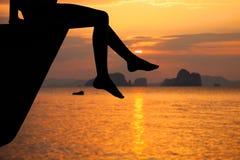 Muchacha adolescente feliz que se sienta en la playa en el tiempo del amanecer Imágenes de archivo libres de regalías