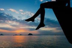 Muchacha adolescente feliz que se sienta en la playa en el tiempo del amanecer Fotografía de archivo libre de regalías