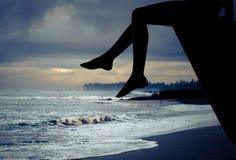 Muchacha adolescente feliz que se sienta en la playa en el tiempo del amanecer Foto de archivo libre de regalías