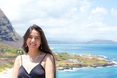 Muchacha adolescente feliz que sonríe con el océano hawaiano en fondo Fotografía de archivo