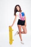 Muchacha adolescente feliz que sostiene el monopatín Imágenes de archivo libres de regalías