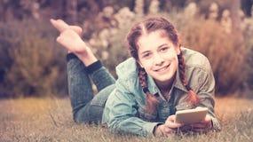 Muchacha adolescente feliz que usa la tableta digital Foto de archivo