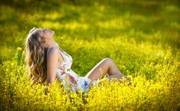 Muchacha adolescente feliz y atractiva en campo del canola Foto de archivo