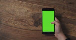 Muchacha adolescente femenina que sostiene smartphone con la pantalla verde sobre la tabla de madera Imagen de archivo