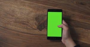 Muchacha adolescente femenina que sostiene smartphone con la pantalla verde sobre la tabla de madera Foto de archivo