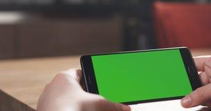 Muchacha adolescente femenina que usa smartphone con la pantalla verde que se sienta en la tabla Foto de archivo