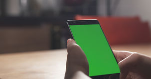 Muchacha adolescente femenina que usa smartphone con la pantalla verde que se sienta en la tabla Fotos de archivo libres de regalías