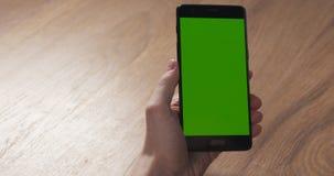 Muchacha adolescente femenina que usa smartphone con la pantalla verde que se sienta en la tabla Imágenes de archivo libres de regalías