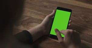 Muchacha adolescente femenina que usa smartphone con la pantalla verde que se sienta en la tabla Imagen de archivo libre de regalías
