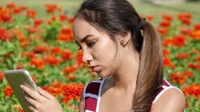 Muchacha adolescente femenina seria que usa la tableta Imagenes de archivo