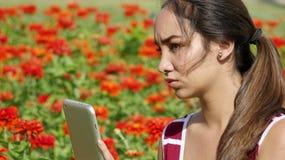 Muchacha adolescente femenina seria que usa la tableta Fotografía de archivo libre de regalías