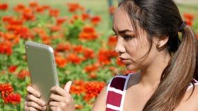 Muchacha adolescente femenina seria que usa la tableta Imagen de archivo