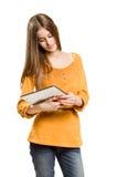 Muchacha adolescente fresca que usa el dispositivo de la tablilla. Imagen de archivo
