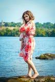 Muchacha adolescente hermosa, colocándose en un acantilado de piedra en agua de río Fotografía de archivo