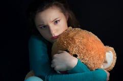 Muchacha adolescente hermosa con el oso de peluche en la oscuridad Imágenes de archivo libres de regalías