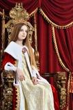 Muchacha adolescente hermosa con la corona que se sienta en butaca del vintage Imágenes de archivo libres de regalías