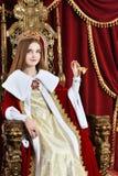 Muchacha adolescente hermosa con la corona que sostiene la campana de mano mientras que se sienta Fotografía de archivo