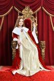 Muchacha adolescente hermosa con la corona que sostiene la campana de mano mientras que sienta i Fotos de archivo
