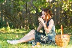 Muchacha adolescente hermosa con una cesta en un jardín que huele una flor Foto de archivo libre de regalías