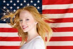 Muchacha adolescente hermosa contra indicador americano Imagen de archivo
