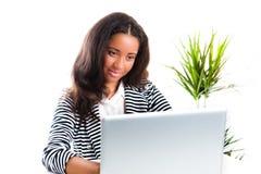 Muchacha adolescente hermosa de la raza mezclada que trabaja en una computadora portátil Imagen de archivo libre de regalías
