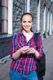 Muchacha adolescente hermosa del estudiante con el teléfono y la mochila Foto de archivo libre de regalías