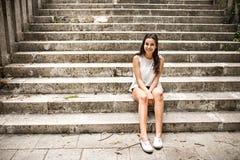 Muchacha adolescente hermosa del estudiante que se sienta en los pasos de piedra Imagenes de archivo