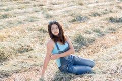 Muchacha adolescente hermosa en campo con la paja Foto de archivo libre de regalías