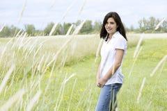 Muchacha adolescente hermosa en campo herboso Fotos de archivo