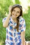 Muchacha adolescente hermosa en el parque en la hierba verde. Foto de archivo