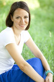 Muchacha adolescente hermosa en el parque en la hierba verde. Imagen de archivo libre de regalías