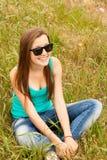 Muchacha adolescente hermosa en el parque en la hierba verde. Imagen de archivo