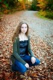 Muchacha adolescente hermosa en hojas de la caída Foto de archivo