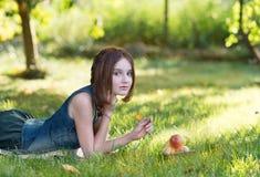 Muchacha adolescente hermosa en la hierba en el jardín con Apple Fotografía de archivo libre de regalías