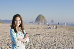 Muchacha adolescente hermosa en la playa cerca de la roca del Haystack Fotos de archivo