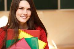Muchacha adolescente hermosa en la sonrisa feliz de la sala de clase Fotografía de archivo libre de regalías