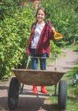 Muchacha adolescente hermosa en los wellies que trabajan en jardín Foto de archivo