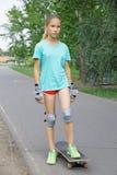 Muchacha adolescente hermosa en un monopatín Foto de archivo libre de regalías