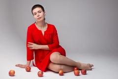 Muchacha adolescente hermosa en un vestido rojo con las manzanas Imagenes de archivo