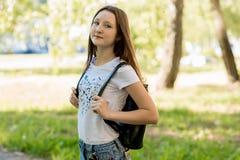 Muchacha adolescente hermosa en verano en un parque al aire libre en sombra de un árbol Vestido en ropa casual Detrás de la mochi Fotografía de archivo