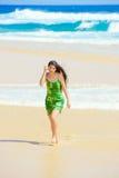 Muchacha adolescente hermosa en vestido verde que camina a lo largo de la playa hawaiana Imagenes de archivo